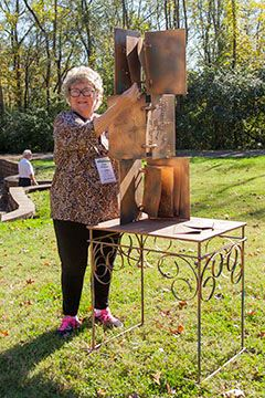 Carol Sue Horstman Posed Next to Book of Knowledge Sculpture